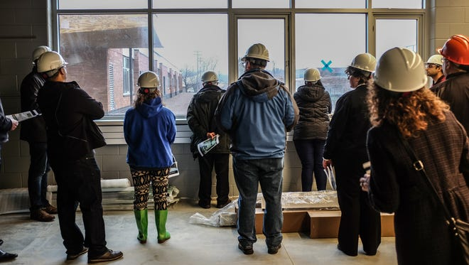 Lansing School Board members look out the large window in one of the project labs at the new renovated and expanded Fairview school site Saturday, April 14, 2018.