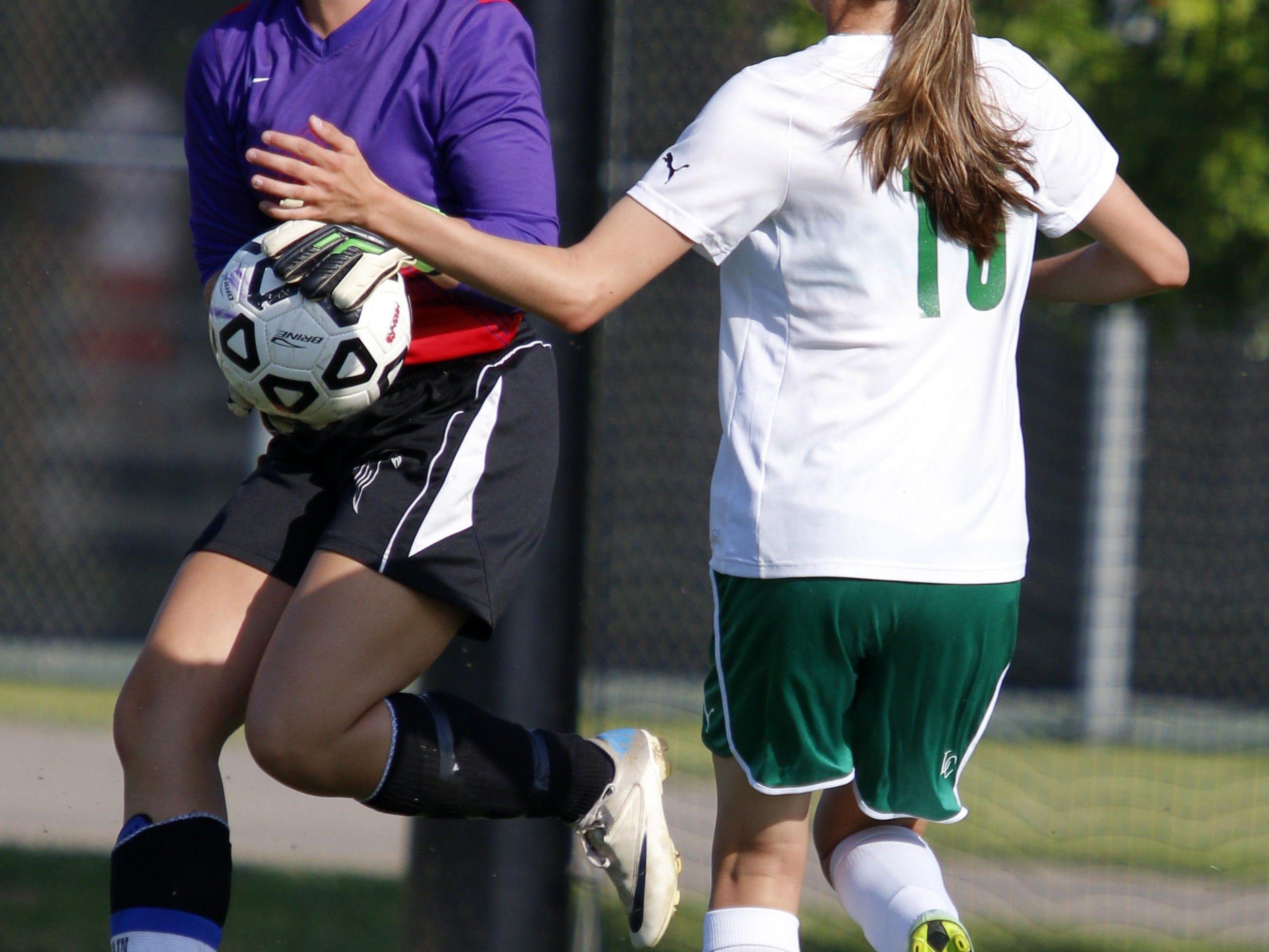 Leslie goalie Sadie Prieskorn, left, stops a shot in front of Jackson Lumen Christi's Riley Raburn in their soccer regional game, Wednesday, June 3, 2015, in Williamston, Mich.