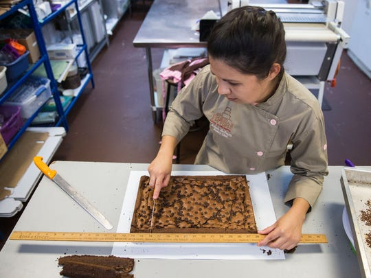 Milena DePaula measures out each cut for brownies at Vanilla's Cakes & Desserts in Bonita Springs, Fla. on Monday, May 7, 2018.