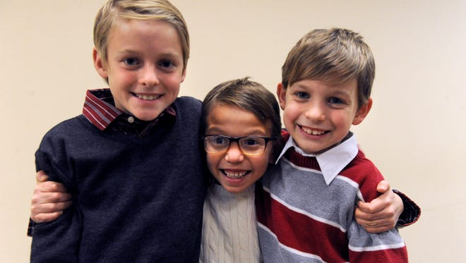 Ray Bearden, 7, hugs his two new brothers Hudson (left), 11, and Carter, 9 Friday at the Taylor County Courthouse. Ray's adoption by Zack and Jamie Bearden was finalized Friday.