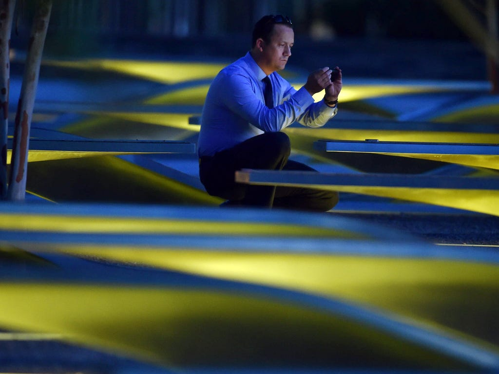 An unidentified man takes photos before sunrise at the National 9\/11 Pentagon Memorial on the 14th anniversary of the 9\/11 attacks.
