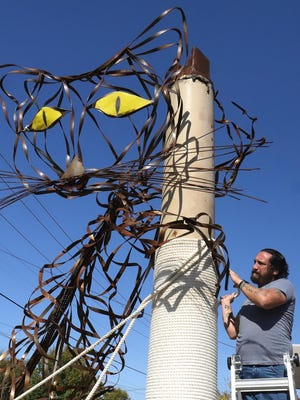Jesse Finwick, Jen's Kitty Rehab co-owner, wraps rope around a giant scratching post, Thursday, Nov. 5, as part of the Robbie Wellborn metal cat sculpture erected in front of the facility under construction across from Ramsey Junior High, 3123 Jenny Lind. Fenwick said that the scratching pole is 15-feet tall and the cat sculpture measures 24-feet from nose to tail. Jen's Kitty Rehab is scheduled for an early 2021 soft opening.