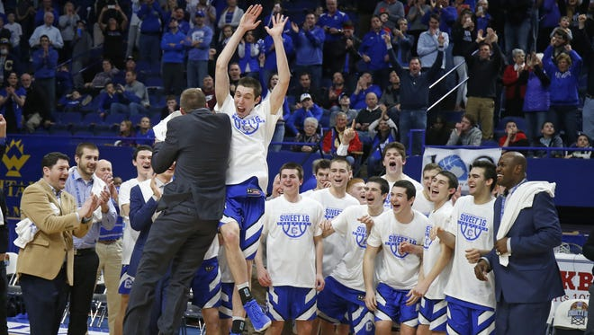 Covington Catholic's C.J. Fredrick, center, celebrates winning the MVP award following the team's win over  Scott County in the championship game of the Whitaker Bank/KHSAA Boys' Sweet 16 basketball tournament played at Rupp Arena in Lexington, Ky. Sunday March 18, 2018.