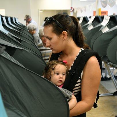 Melissa Harper, carrying her 7-month-old daughter Merritt,