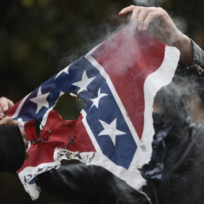 A masked protester burns a Confederate flag at UTK
