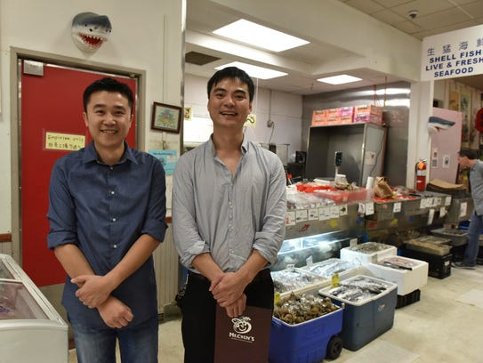 Jason Lin and Fisher Yu of Mr. Chen's grocery and restaurant pose adjacent to the store's seafood market.