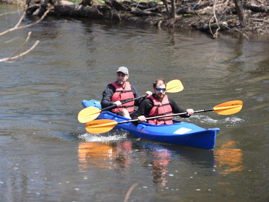 Mike Kane and Nolan Holmes paddle to the dock after