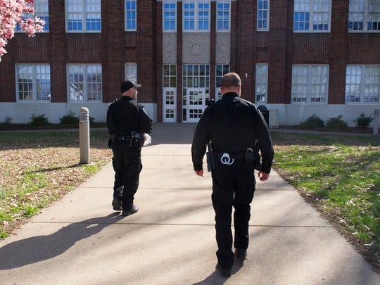 Evansville Police Officers Craig Pierce, left, and Rick Bagby both of Evansville, enter Lincoln Elementary School Thursday.