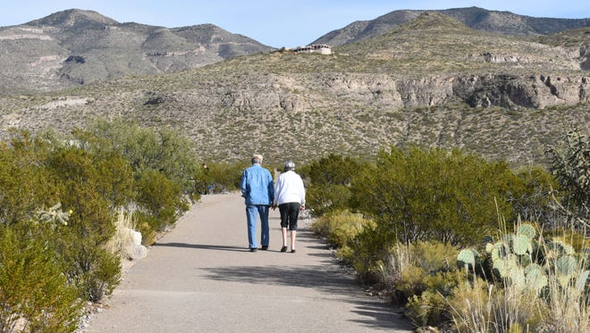A couple walks hand in hand on the Desert Foothills Park during the annual Turkey Time Walk Monday.