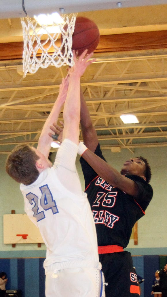 Spring Valley's Mavenson Therneus goes up for a shot against Saunders' Sean Bresnan during Wednesday's game at Saunders High School.