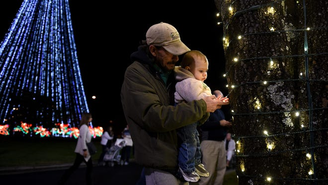 Brian Hinchee hold his son Spencer Nichols, 11 months, during Gaylord Opryland Resort & Convention Center's lighting ceremony Thursday, Nov. 19, 2015.