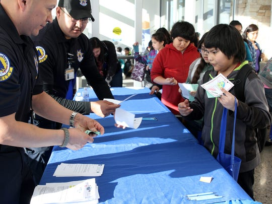 "Nicholas Tso, right, a fifth-grader at Apache Elementary School, takes part in an exercise in which students pretend to register for college classes during Shi'yaz'hi ""My Little One"" College Day on Fridayat the south campus of Diné College in Shiprock. At left are security guards Adrian Lewis and Cherokee Dee serving in the role of college administrators."