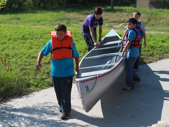Campers help their camp mentor lower a canoe into the