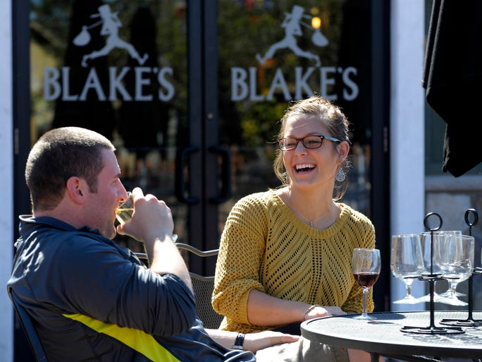 Payton Kaminski  shares a laugh with her boyfriend, Mike Simpson,  both of Oxford, as he drink Flannel Mouth Hard Cider and she drinks Blue Berry Fields Wine. Patrons gather at Blakes's Hard Cider Co., in Armada Township Wednesday afternoon, Sept.24, 2014, as hard cider continues to gain popularity across the United States.