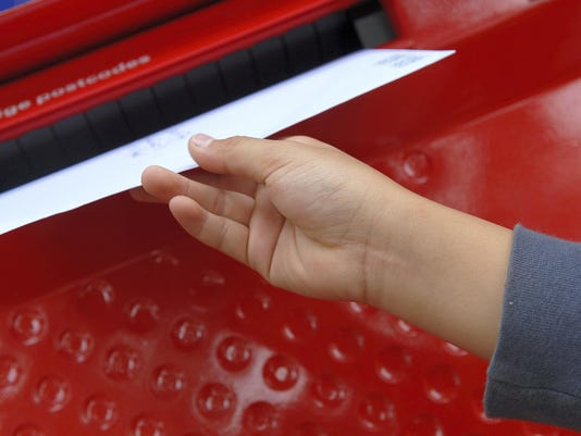 Close-up of a woman's hand dropping mail into a mail slot