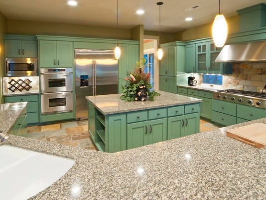 A modern kitchen that has sage colored cabinets