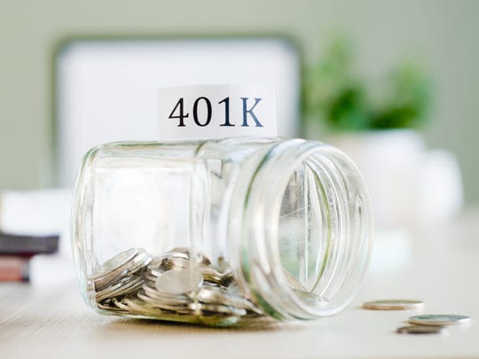 Tipped over glass jar full of coins that's labeled 401(k)
