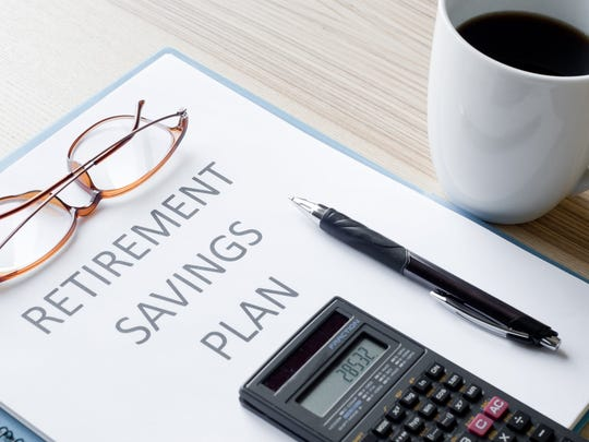 "A mug of coffee and a binder labeled ""RETIREMENT SAVINGS PLAN"" with a calculator, pen, and pair of eyeglasses on it."