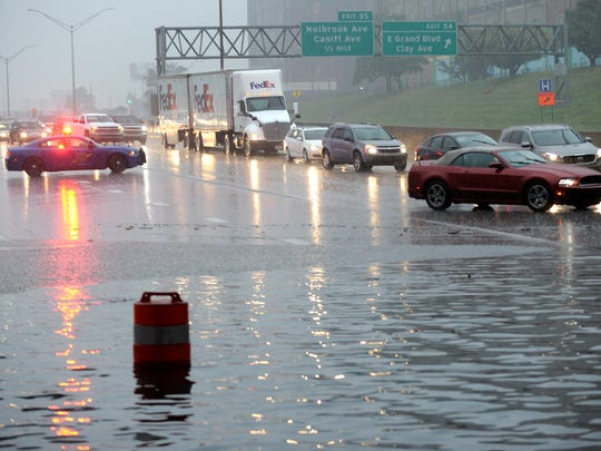 Southbound I-75 traffic is forced into the passing lane as motorists drive slowly through floodwater under East Grand Boulevard in Detroit. The tri-county area is under a flash flood warning.