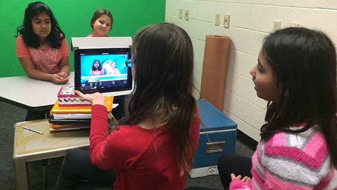 Sahana Premnath, back left, and Dolce Rusniaczek are the commentators for a film being created in the STEM Academy's Green Screen Room about project-based learning. Helen Conran front left, holding iPad, and Stephanie Kocos are the camera people for this production.