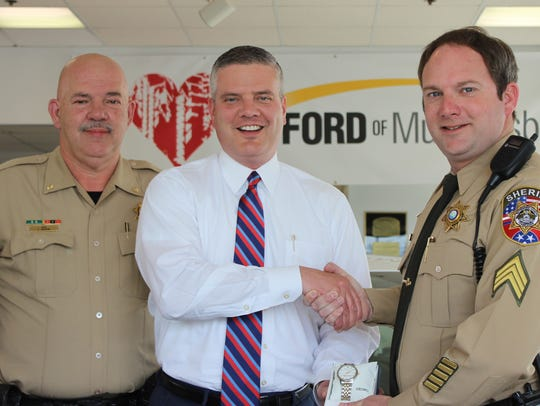 Sheriff's Sgt. Trey Nunley, right, receives an engraved