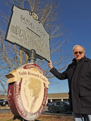Ray Thompson, director of the Nabb Research Center at Salisbury University, stands beside a historical plaque that stood in Princess Anne in the 1930s. The plaque is being moved and will be reset in April at the birthplace of Samuel Chase near Allen.