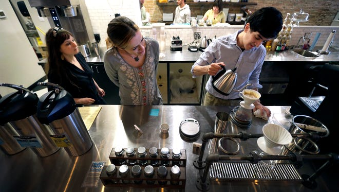 """Manager Noelle McGinnis (left) and co-owner Trish Lison Sheikh train new employee Ivan Arevalo in the art of making a 12-ounce pour-over of """"The Congo,"""" during a training session at Timshel Cafe in downtown Neenah."""