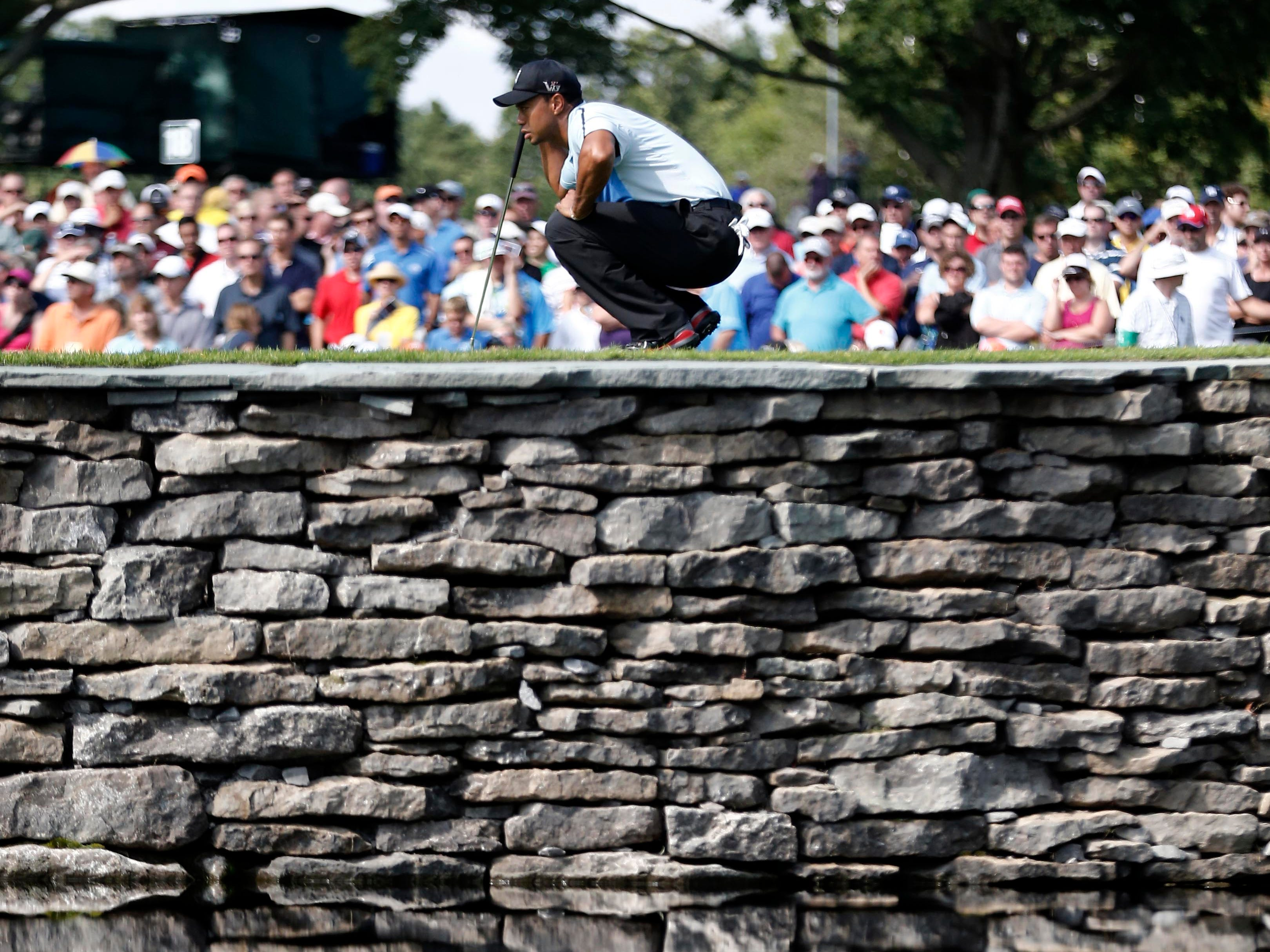 Tiger Woods looks at his birdie putt on the 15th green during the first round of the 95th PGA Championship at Oak Hill Country Club.