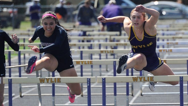 Wylie's Ambria Brekke, right, gets over the final hurdle just ahead of Brownwood's Trinity Buitron in the District 5-4A 100-meter hurdle finals at Bulldog Stadium on Thursday, April 5, 2018. Brekke also qualified in the 300-meter hurdles.