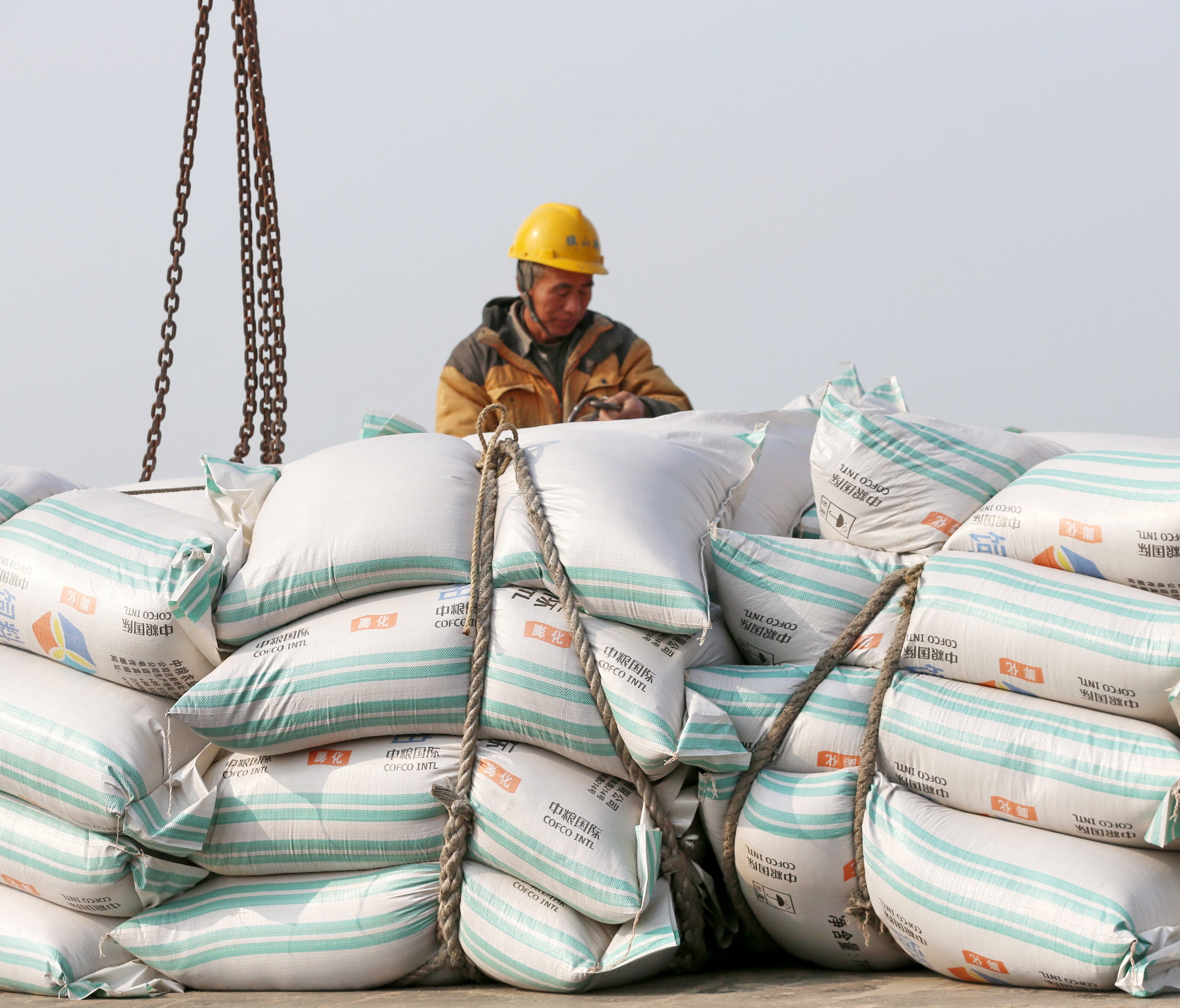 A worker moves bags of soybean meal at a port in Nantong, Jiangsu province, China, 22 March 2018 (issued 04 April 2018). China will place 25 percent tariffs on a list of 106 US goods, in a retaliatory action against the US's new tariff on Chinese pro