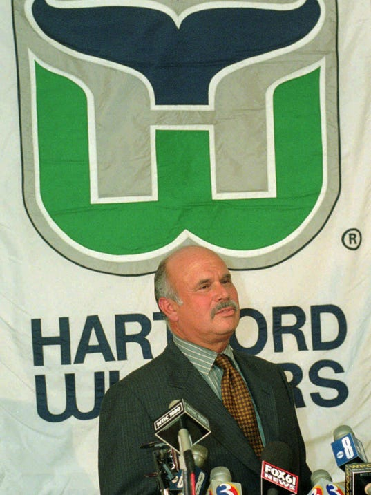 "FILE - In this May 15, 1996, file photo, Peter Karmanos, owner of the NHL hockey team Hartford Whalers, answers a question during a news conference in Hartford, Conn. The new owner of the Carolina Hurricanes has a soft spot for his team's old identity _ the Hartford Whalers. In the month since Tom Dundon assumed control of the Carolina Hurricanes, from Karmanos, they've brought back ""Brass Bonanza,"" stocked the shelves in the team store with that beloved whale-tail logo and have discussed bringing back the Whalers, too _ if only for a future turn-back-the-clock night. (AP Photo/Bob Child, File)"