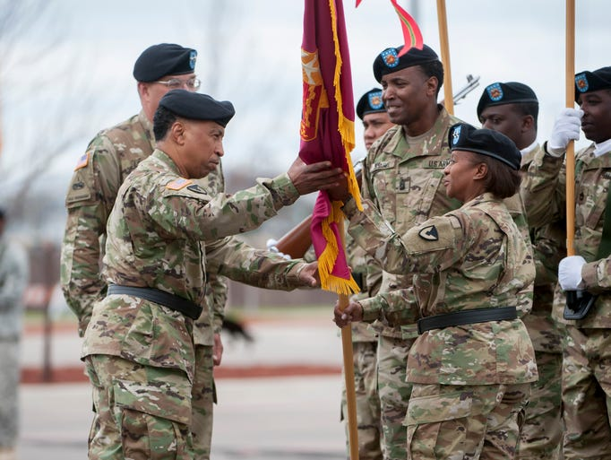 Officiator Gen. Dennis Via, left, receives the colors
