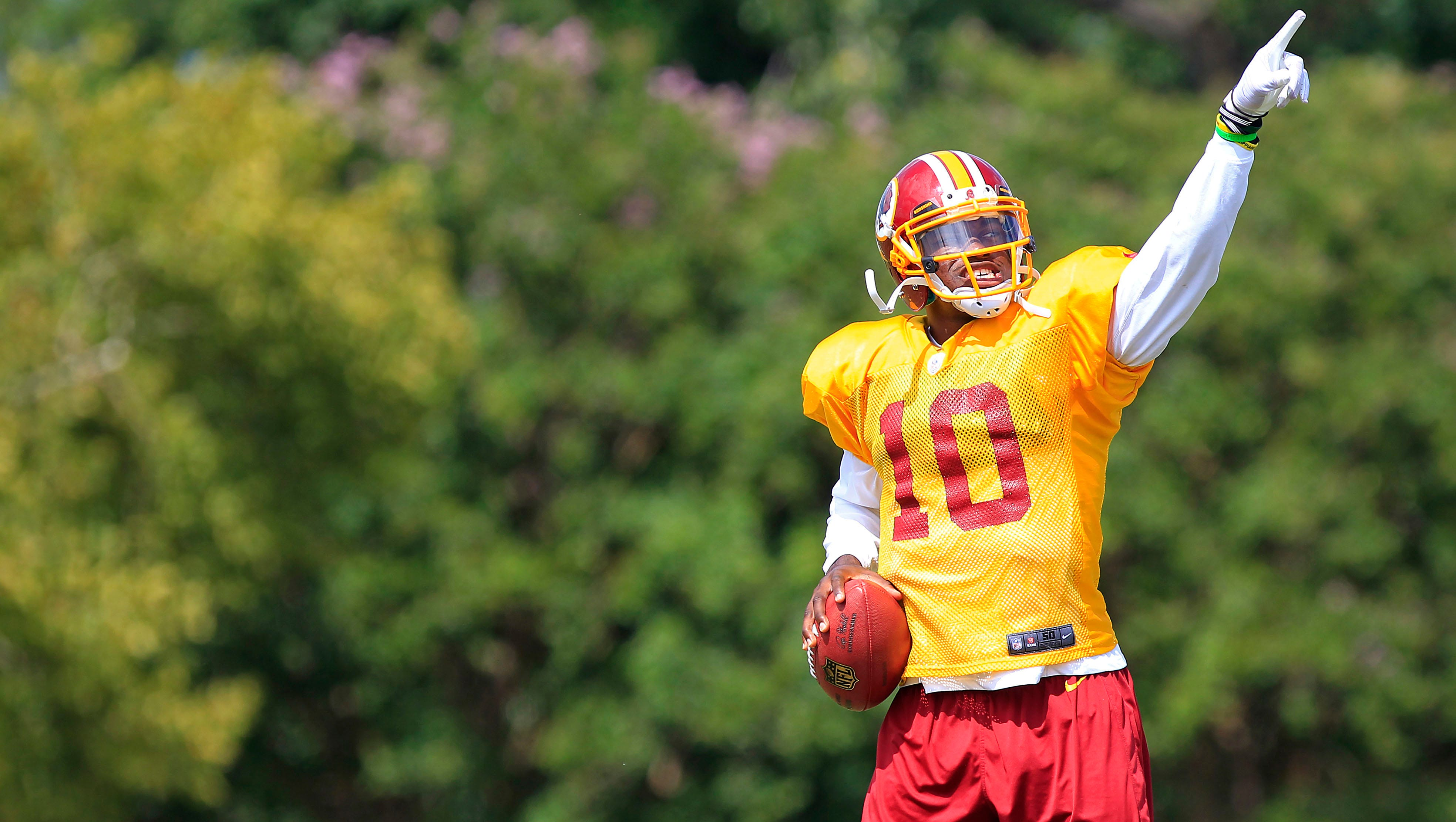 Washington Redskins quarterback Robert Griffin III (10) gestures prior to throwing the ball during afternoon practiceon Aug. 13.