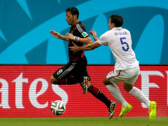 United States' Matt Besler chases Germany's Mesut Ozil along the sidelines during the group G World Cup soccer match between the United States and Germany at the Arena Pernambuco in Recife, Brazil, Thursday, June 26, 2014. (AP Photo/Julio Cortez)