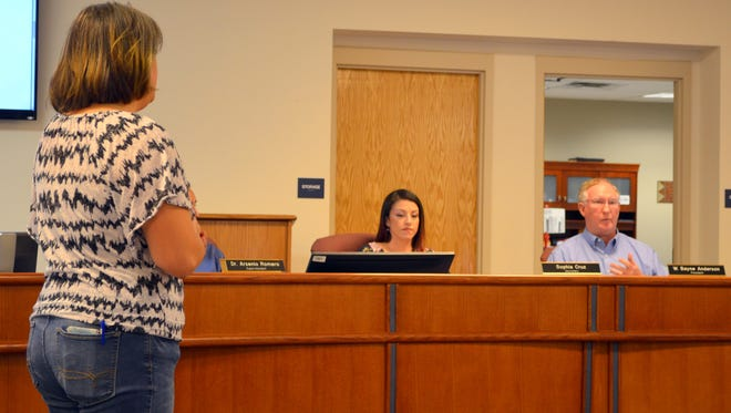 At left, Charity Cheung, co-president of the National Education Association -Deming, addresses the Deming Public Schools Board of Education. In background, from left, are Secretary Sophia Cruz at board president W. Bayne Anderson during Thursday's school board meeting.