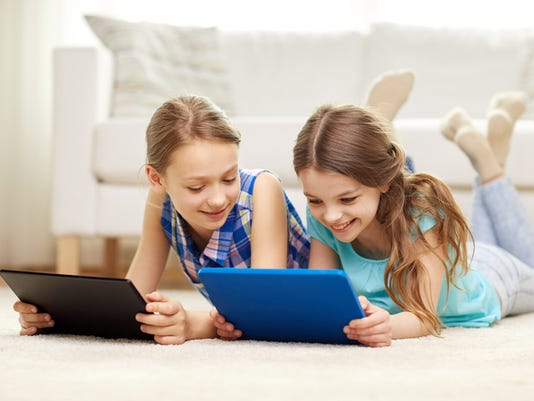 happy girls with tablet pc lying on floor at home