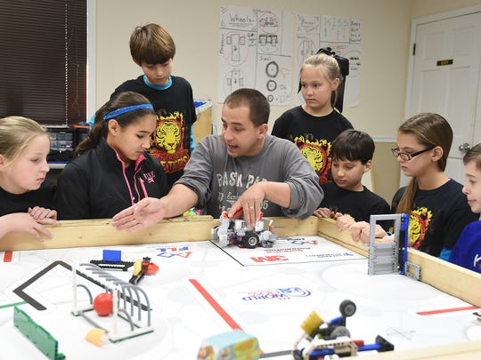 Greg Davis (center), coach of the Mountain Home FireTigers FIRST LEGO League robotics team, shows team members the route their robot will take during practice. The team and 31 others will compete in the Arkansas State FLL tournament on Saturday at The Sheid on the campus of Arkansas State University Mountain Home. The robot part of the competition begins around noon. Pictured with Davis are; (from left) Elizabeth Harris, Charlotte Watson, Asa Norwick, Audrie Corcoran, Eric Davis, Kate Davis and Gage Simmons. Not pictured is Duncan Conly.
