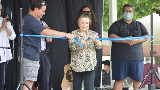 Bluegrass-gospel legend Janis Lewis Phillips cut the ribbon opening the recent bluegrass festival at the Lewis Family Homeplace near Lincolnton, Ga.