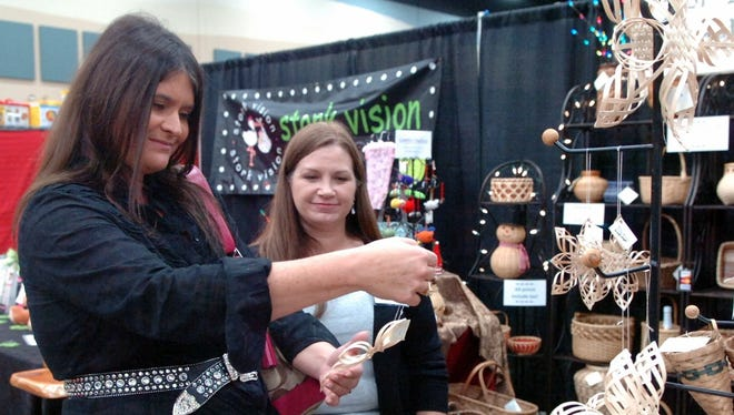 Shannon Cunningham looks over the wooden ornaments Jenny Antoline sells at her Gypsy Baskets booth at Hangar Holiday in this file photograph. Hangar Holiday will run Nov. 19-20 at the MPEC. The holiday market is presented by the Sheppard Officers Spouses Club.