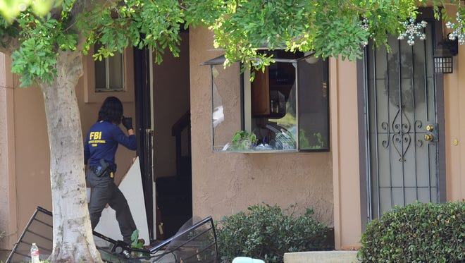A member of an FBI evidence response team walks over a destroyed door to enter a townhome in Redlands, California December 3, 2015 linked to the December 2 shooting rampage in San Bernardino, California. At least 14 people were killed in a gun attack on a holiday party in San Bernardino, in the country's worst mass shooting since the massacre of 26 people at Sandy Hook elementary school in Connecticut in 2012. A heavily armed man and woman killed 14 people and injured at least 17 at a social services center before the suspects died during a shootout with police.  AFP PHOTO /ROBYN BECK