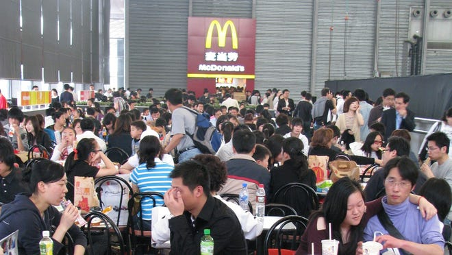 Chinese visitors enjoy a temporary McDonald's outlet at the Shanghai Auto Show venue in April 2009.