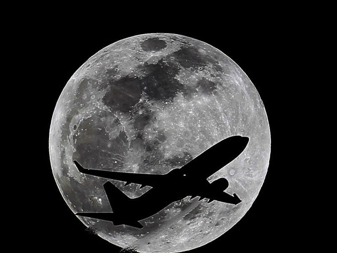 An airliner crosses the moon's path, Monday, April 14, 2014, above Whittier, Calif., approximately one hour before a total lunar eclipse. Then, on April 29, the Southern Hemisphere will be treated to a rare type of solar eclipse. In all, four eclipses will occur this year, two lunar and two solar.