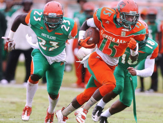 Montavious Wlliams darts through the Green defense for a touchdown on Saturday as the Orange beat the Green, 30-27. Giving chase is Vasty Paul of the Green defense. On a drizzly Saturday afternoon, the FAMU Rattlers played their annual Orange and Green Spring game inside of Bragg Memorial Stadium.