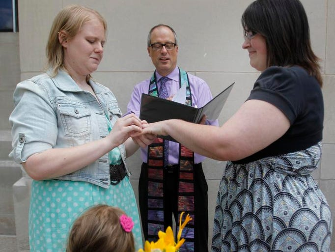 Natalie, left, and Heather Starr, with their daughter Libby, say their vows in front of Rev. Roger Bertschausen on the steps of the Outagamie County administration building on June 9, 2014 in Appleton, Wis. They are the first same-sex couple to be married in the county.