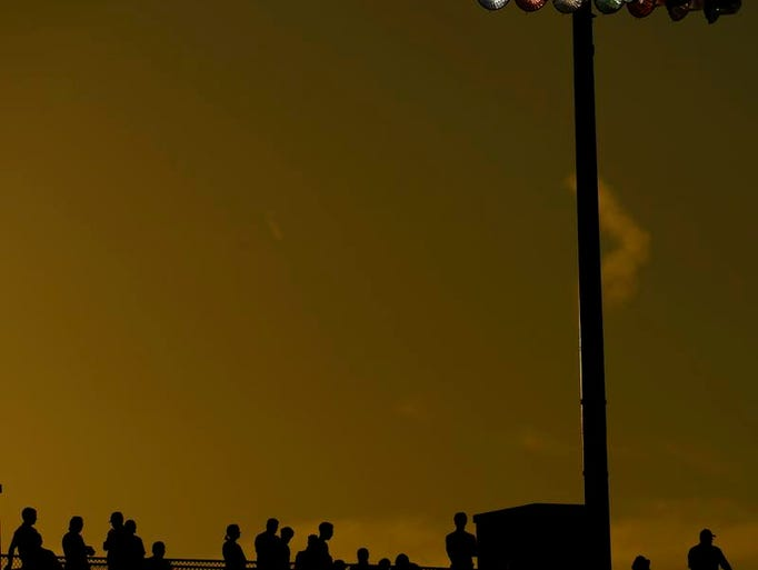 Spectators are silhouetted against a golden sky as they watch the WIAA state track and field championships at Veterans Memorial Field Sports Complex in La Crosse on Friday, June 6, 2014.