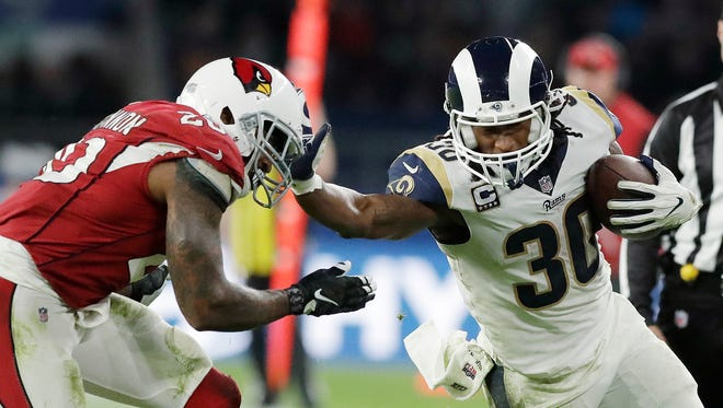 Los Angeles Rams running back Todd Gurley (30) holds off Arizona Cardinals inside linebacker Deone Bucannon (20) during the second half of an NFL football game at Twickenham Stadium, in London, Sunday Oct. 22, 2017.