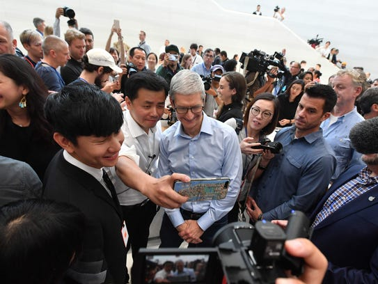 Apple CEO Tim Cook poses for a selfie as people explore