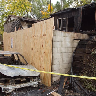The shell of a resident's car burned out by fire sits
