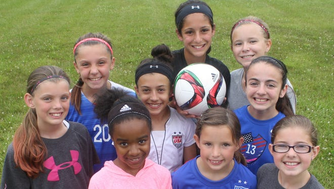 Members of the AC Milan Detroit 12U girls soccer team have been avid fans of the United States as they battle toward a World Cup title. Pictured are (front row from left) Kirsten Jones, Olivia Ahlgren, Reagan Burnette, (middle row from left) Taylor Meadows, Sarah Marasco, Juliana Morrow, (third row from left) Kenzie Hare, Grace Distelrach and Audrey Porter.
