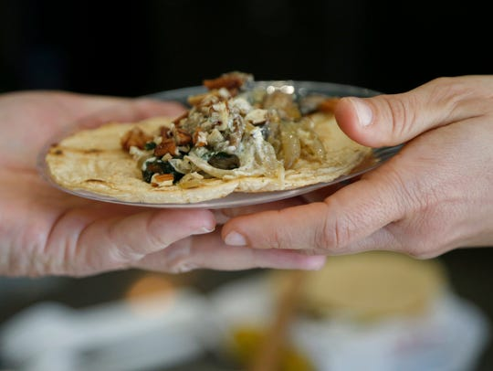 Claudia Zamora serves a pair of tacos at Findlay Kitchen